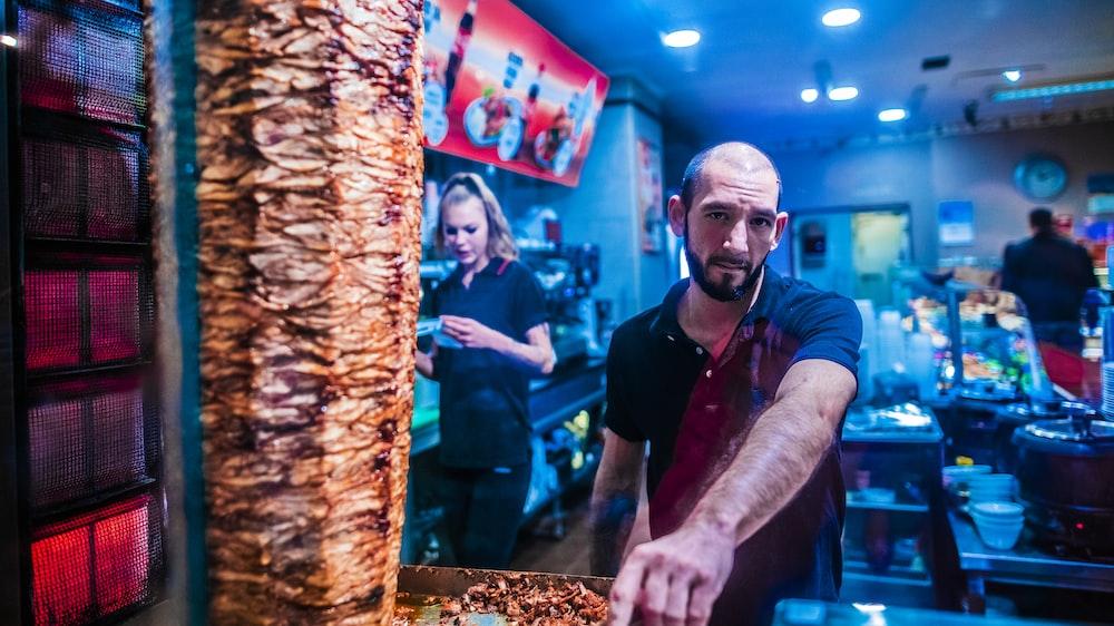 man standing near shawarma