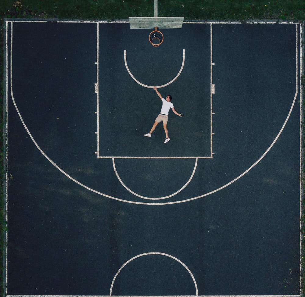man in white shirt lying on outdoor basketball court