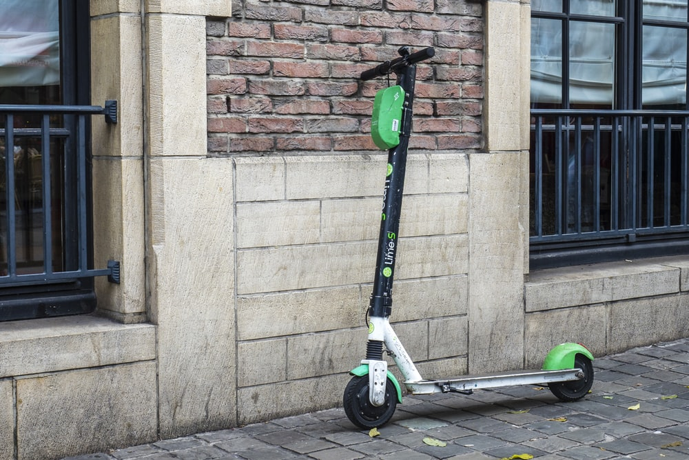 white and green scooter parked beside wall