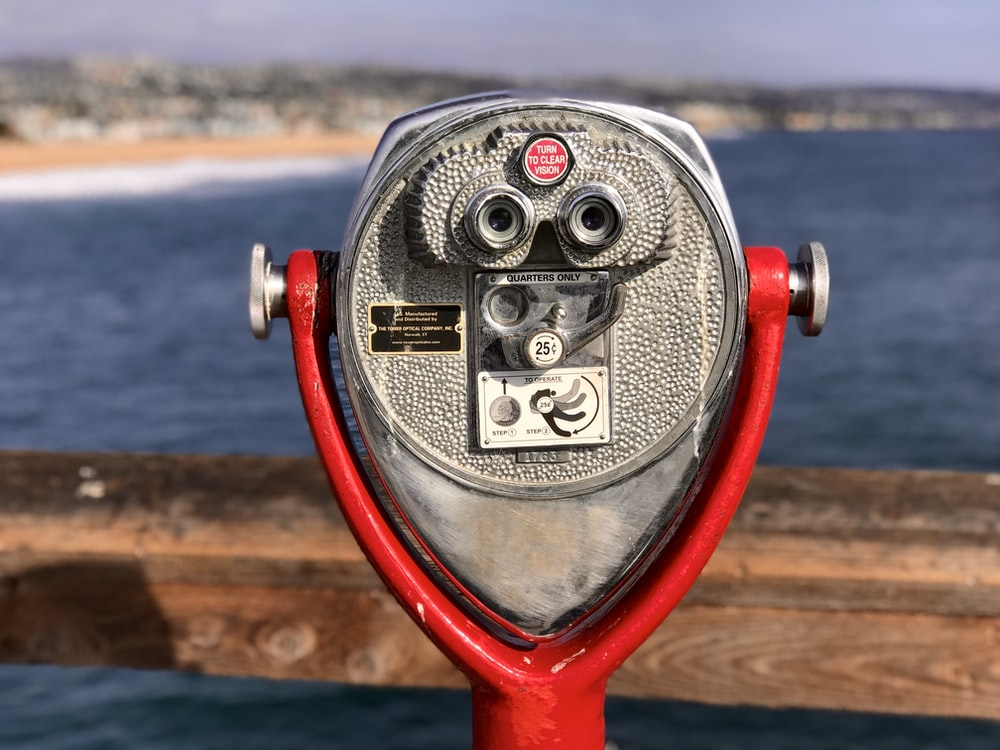 gray stainless steel and red coin-operated telescope viewing blue body of water during daytime