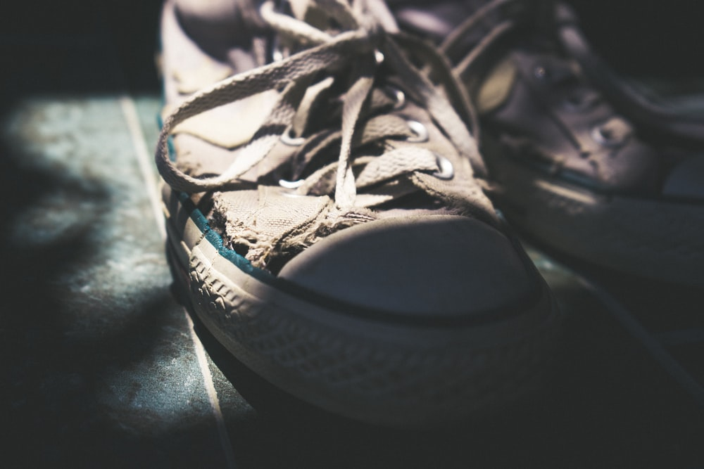 pair of white sneakers with tied shoelace