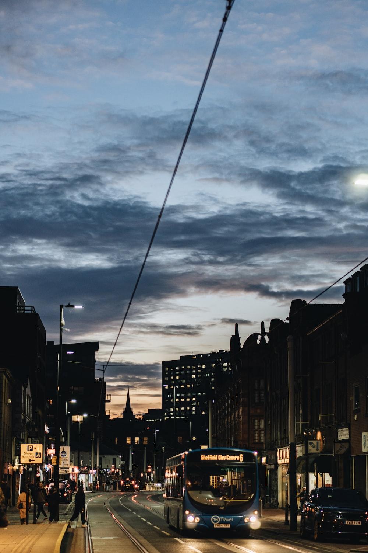 lighted blue bus near black sedan and building during dawn