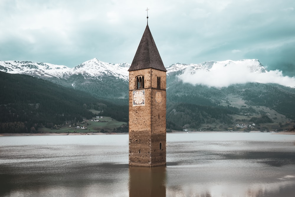 brown concrete tower on body of water during daytime