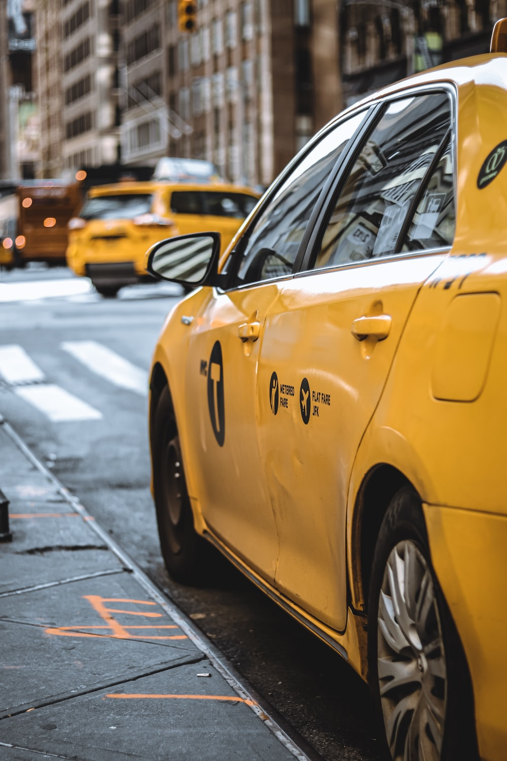yellow taxi parked beside curb