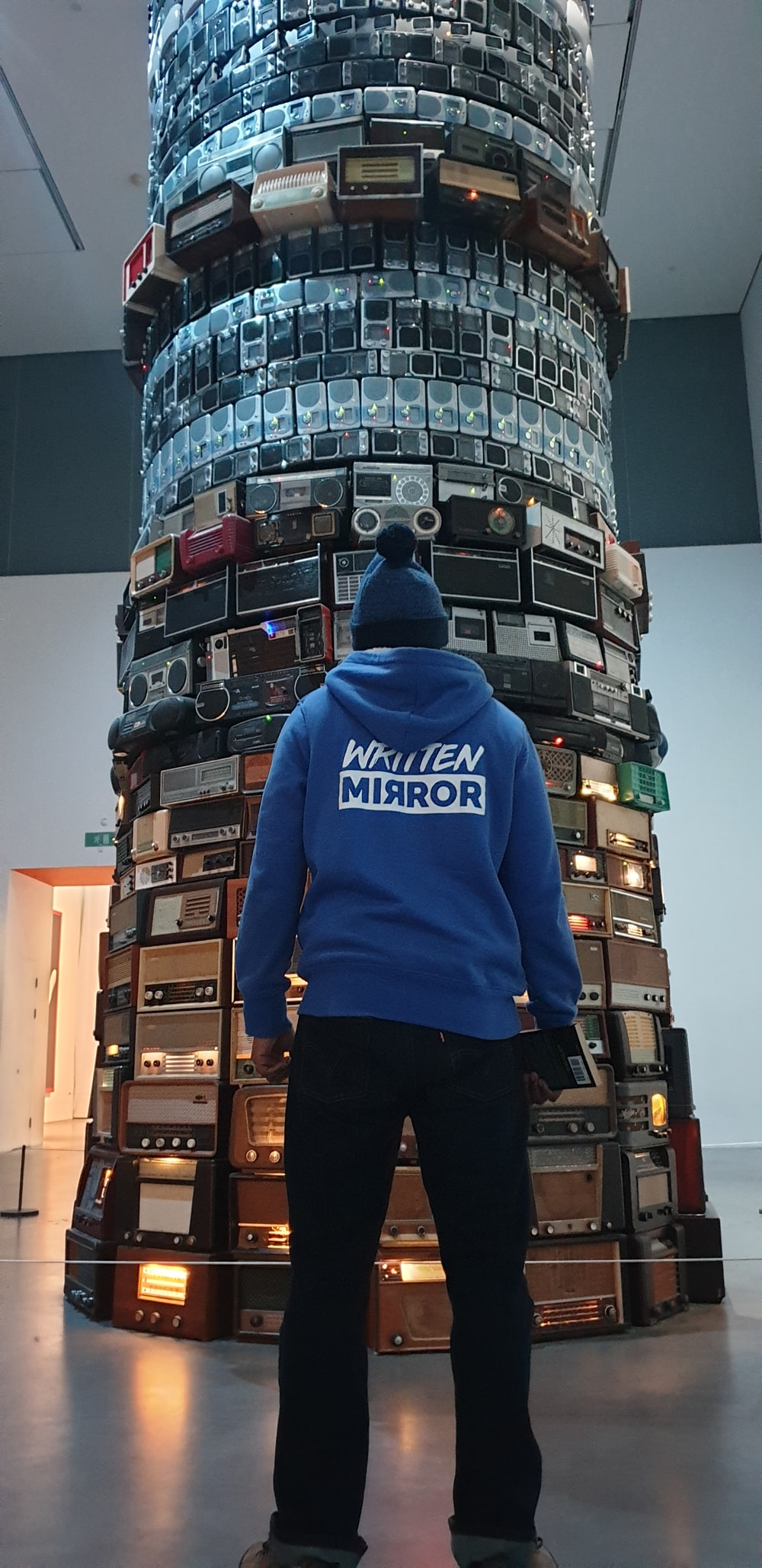 person wearing blue hoodie standing in front of tower