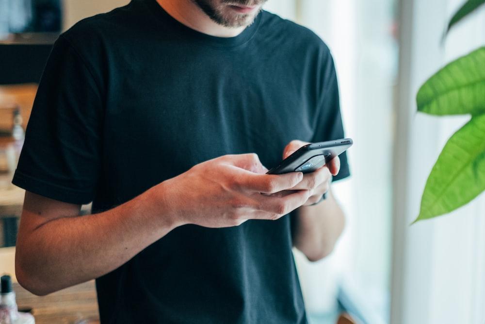 man in black crew-neck top using smartphone