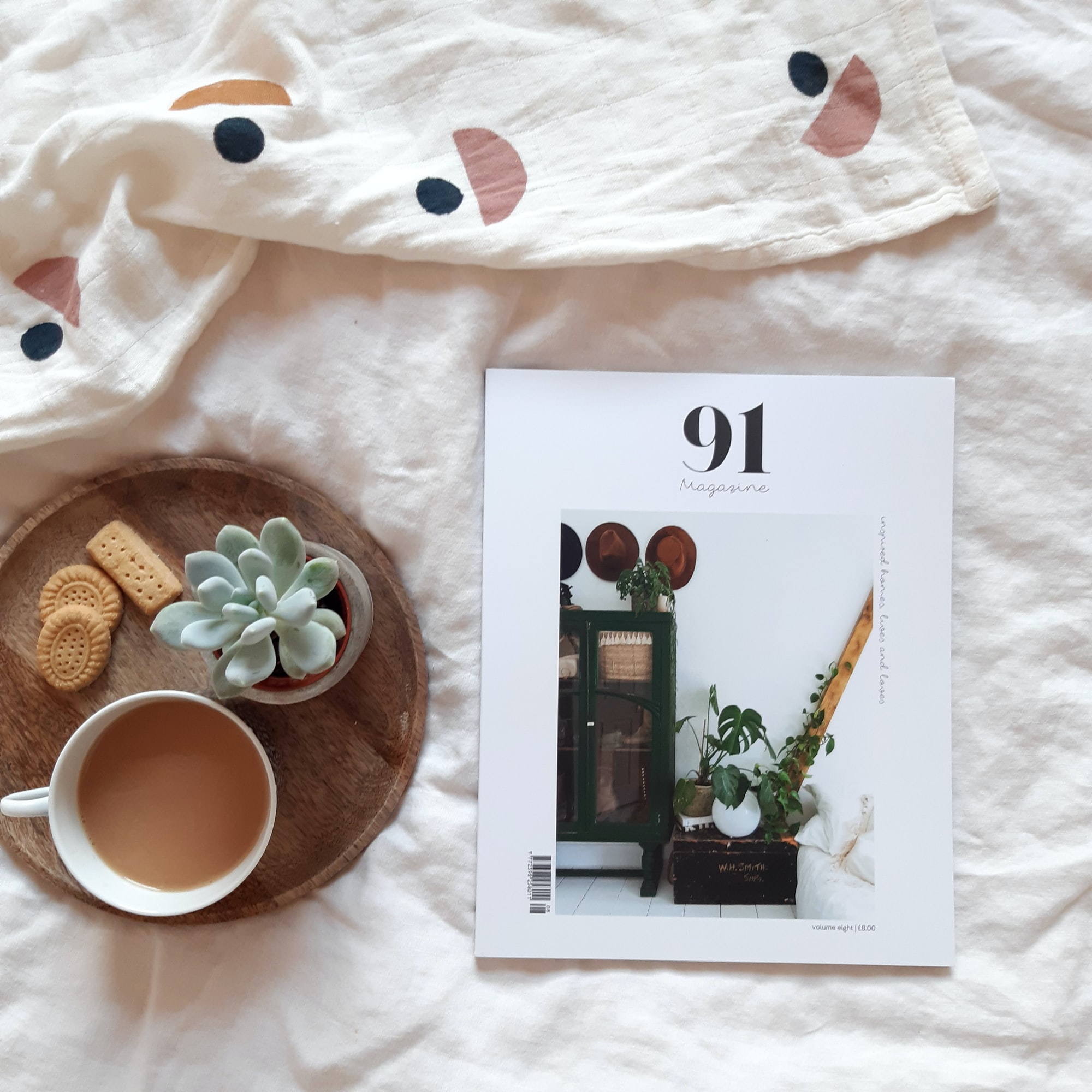 a print magazine about interiors and lifestyle on a bed with a cup of tea and biscuits and succulent on a tray.