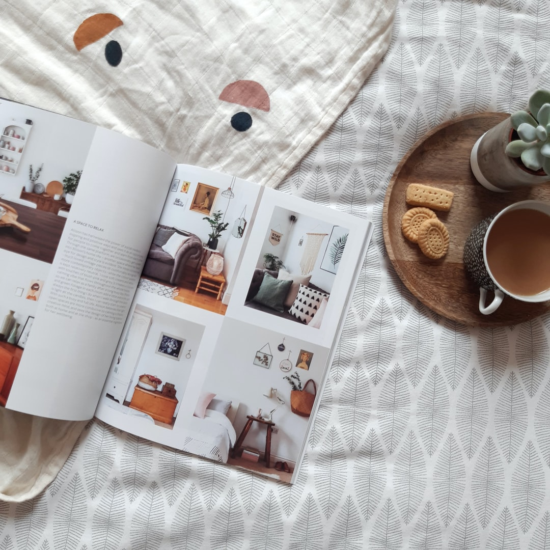 An open magazine on bed, showing beautiful interiors with a cup of tea, biscuits and a succulent plant on a tray.