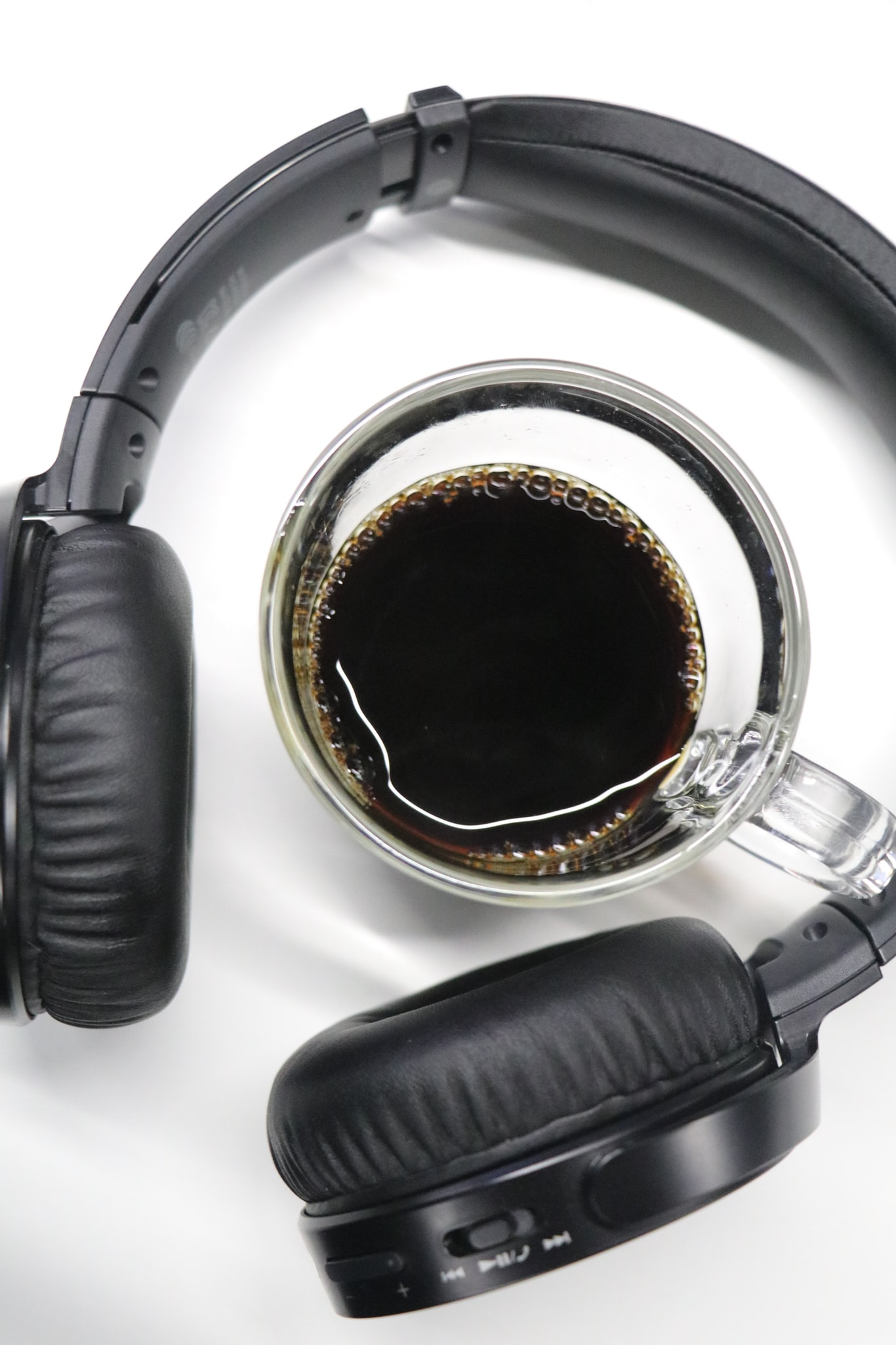 half-filled clear glass cup in black wireless headphones