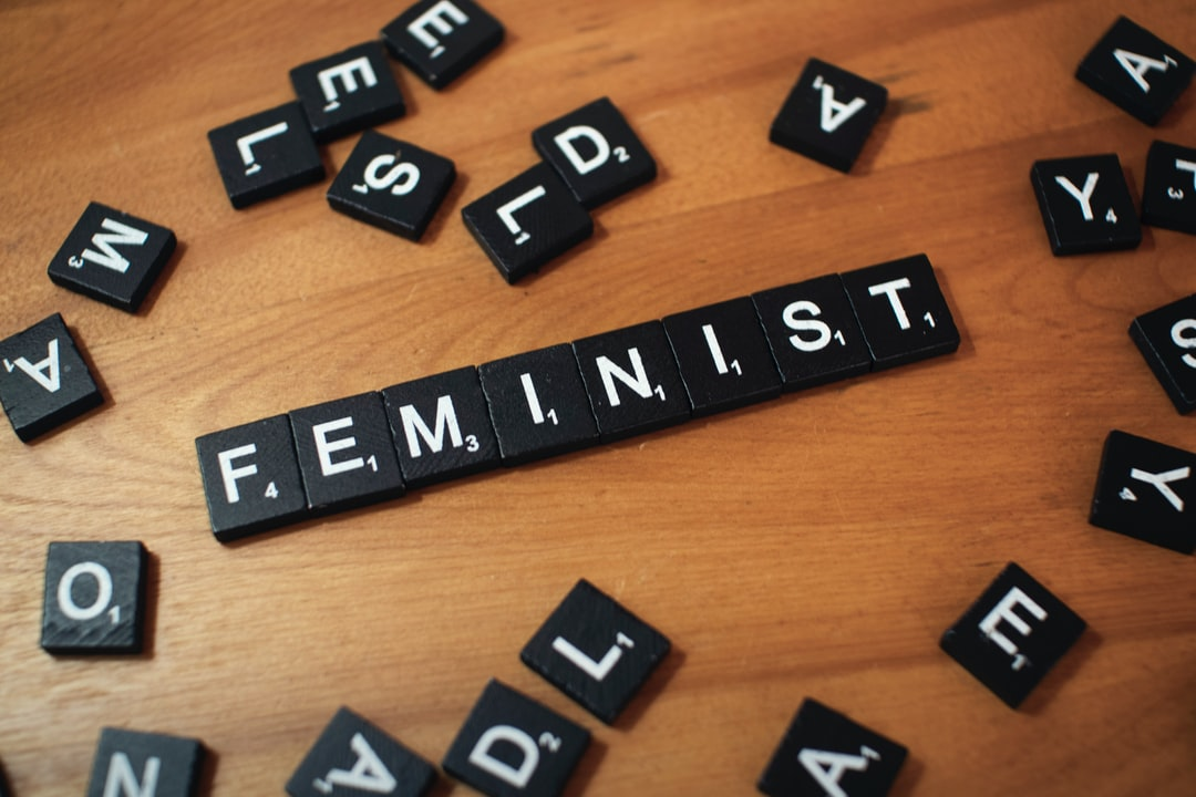 Black and white Scrabble wood letter blocks form the word FEMINIST on a wooden table top surrounded by other game pieces.