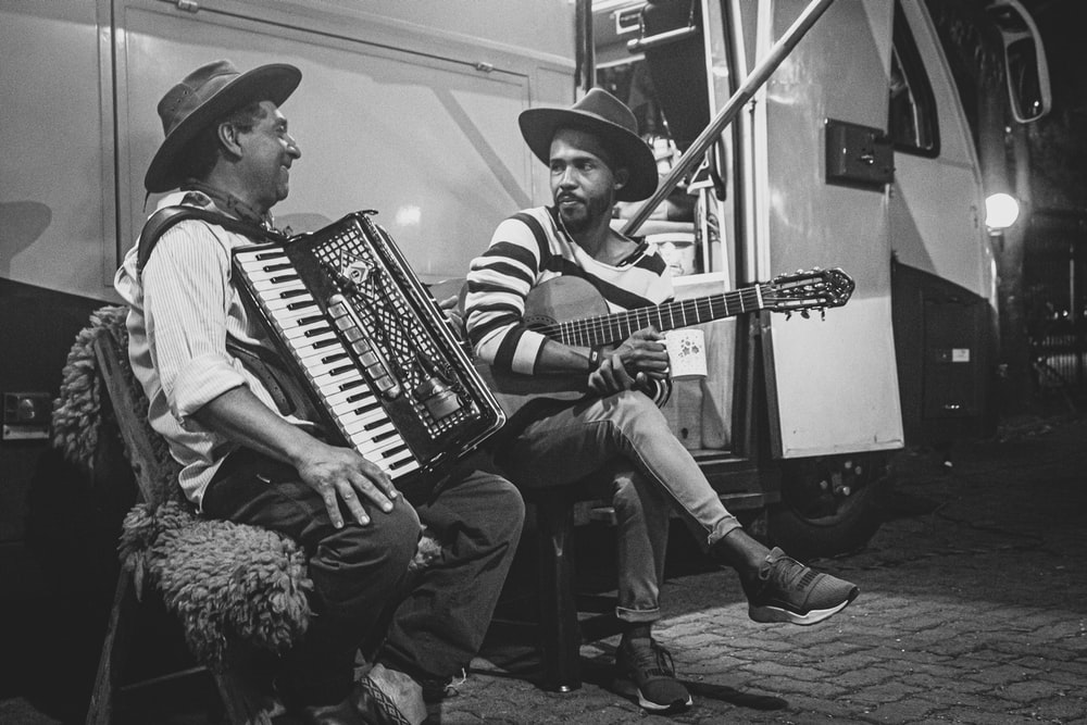 grayscale photo of two man playing musical instrument beside bus