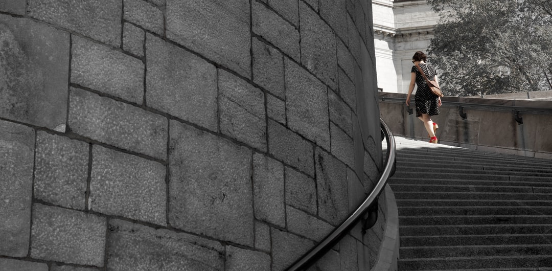 Woman with red shoes walking up circular stairs