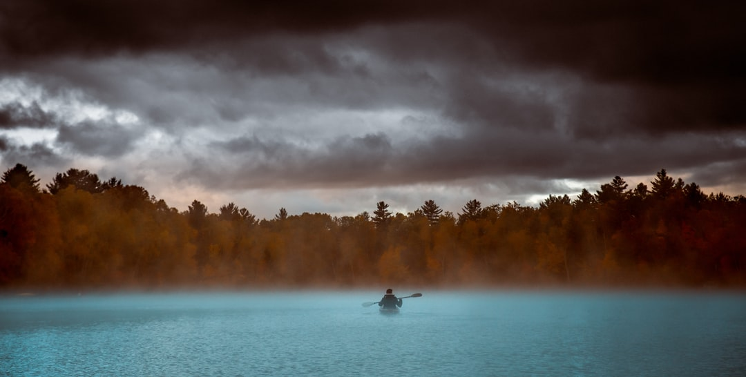 Man kayaking on a lake with fog and dark clouds