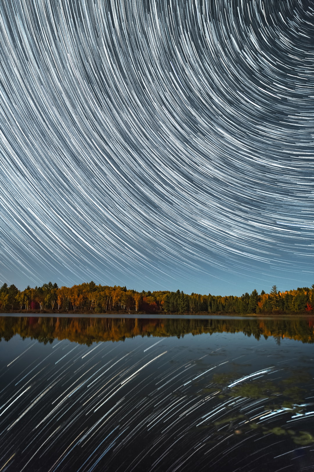 Star trails and reflections over a lake during fall with colourful trees