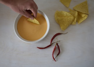 four red chills beside white cup with sauce and yellow chips