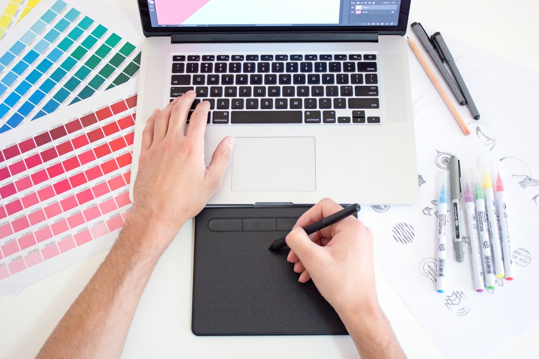 Graphic designer working on a Macbook laptop using a trackpad, color charts and markers