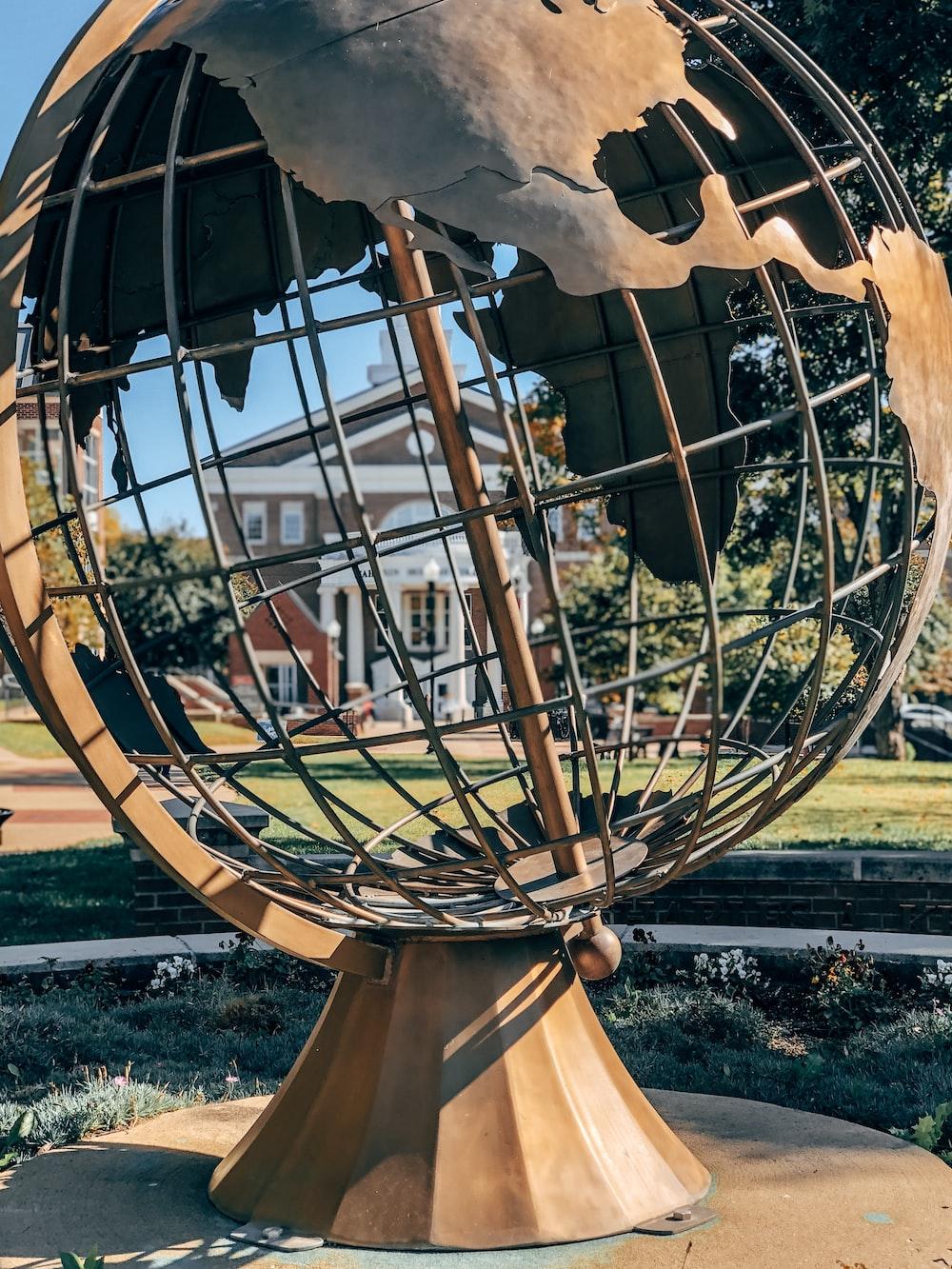 round gray metal globe statue
