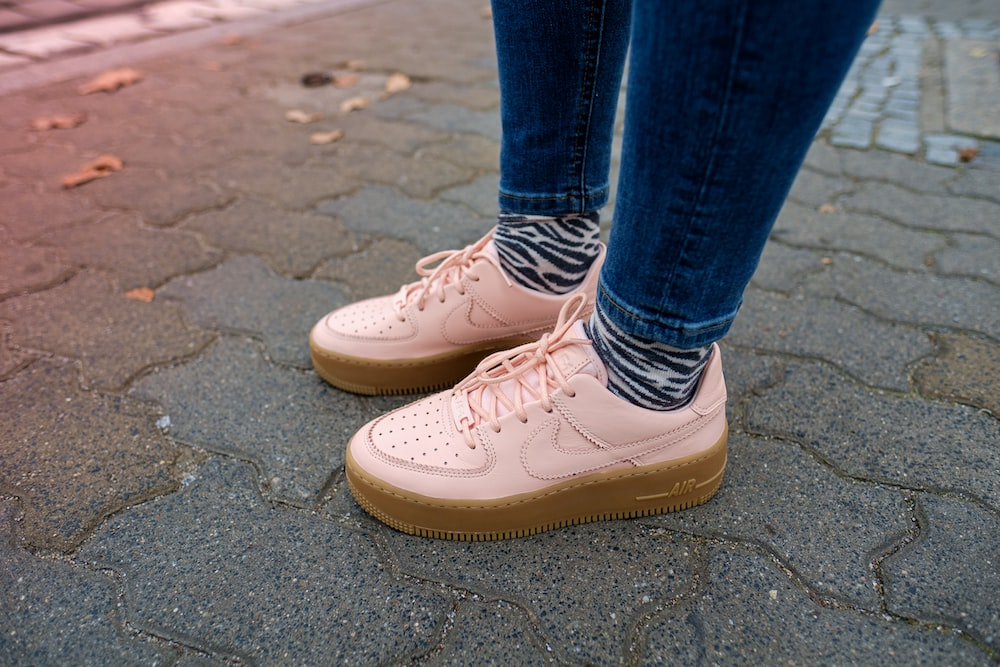 person wearing blue denim jeans and white Nike Air Force low-top sneakers standing