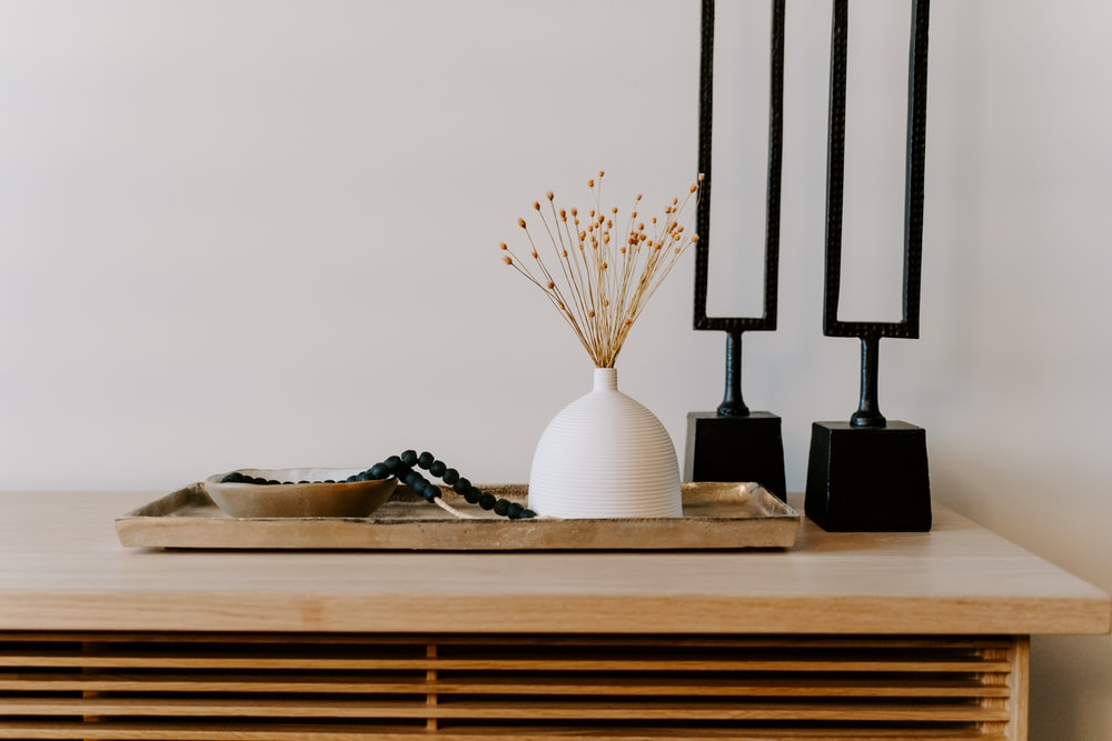 white ceramic vase near two black table decors