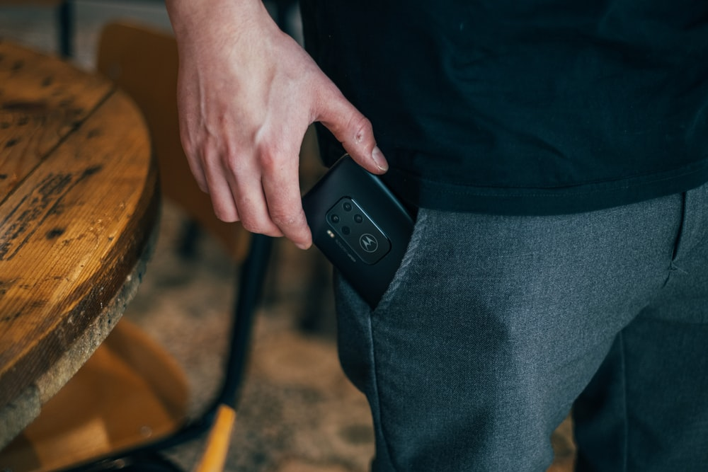 person inserting smartphone in pocket