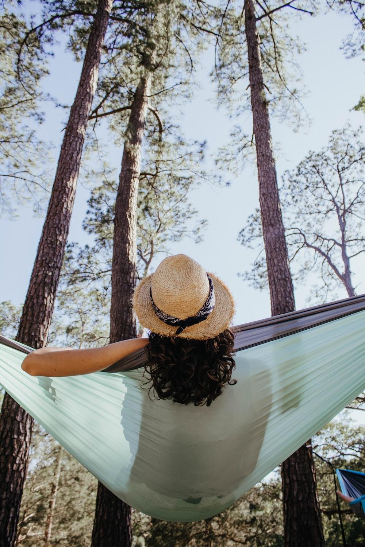 woman sitting on green hammock outdoors