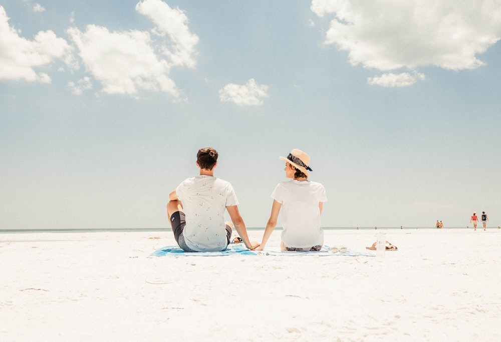 man and woman sitting on shore under blue sky during daytime