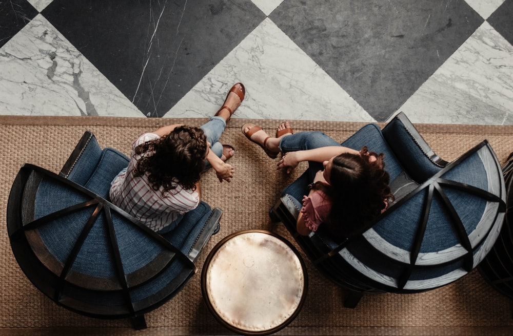 two women sitting on blue armchairs