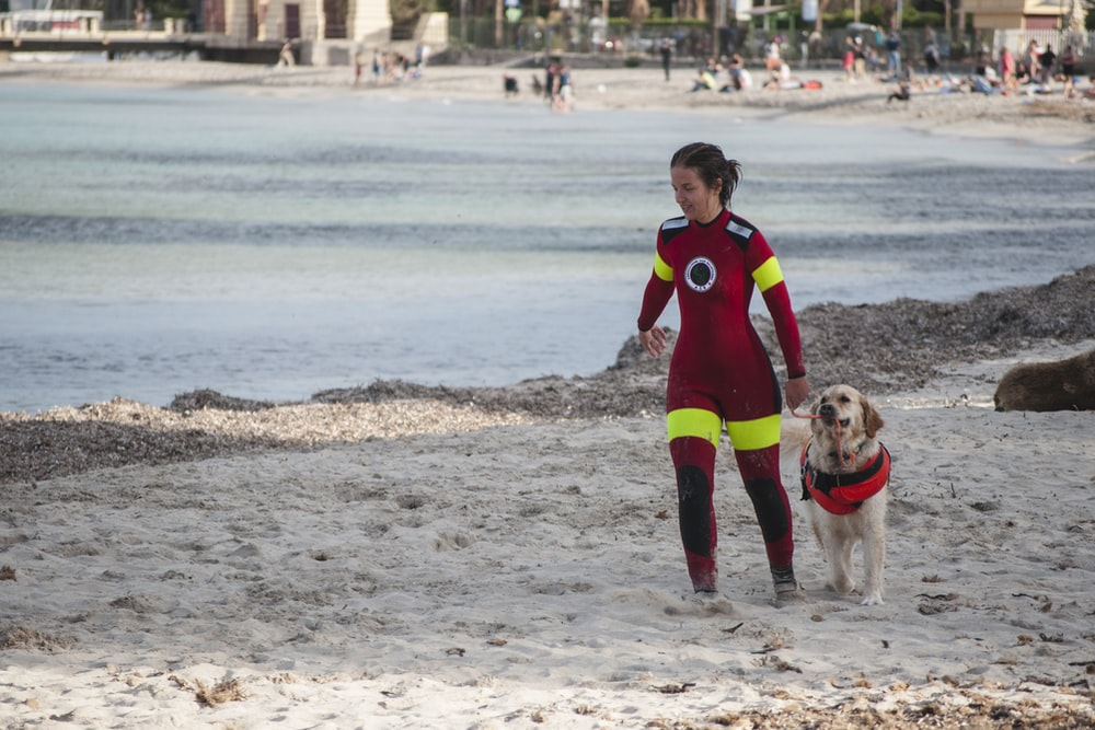 woman in red jumpsuit beside brown dog