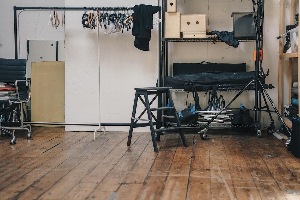 black stool beside clothes rack