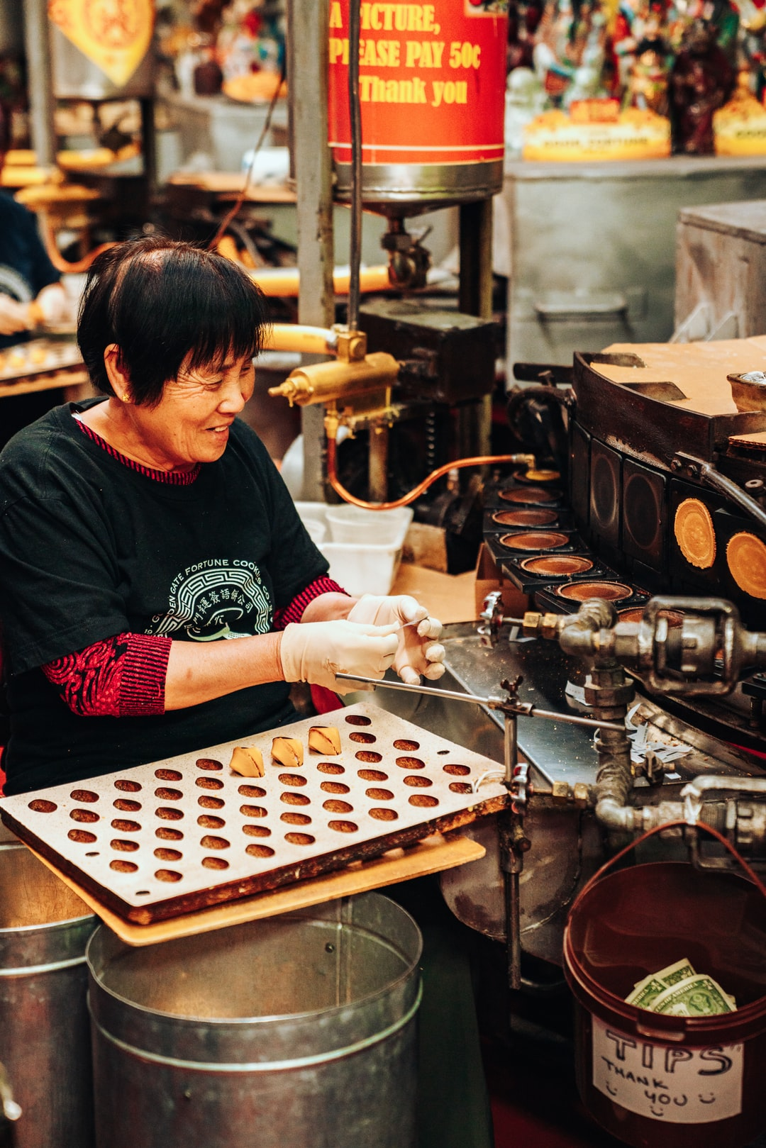 Woman happily making fortune cookies at Golden Gate Fortune Cookie Factory in San Francisco.