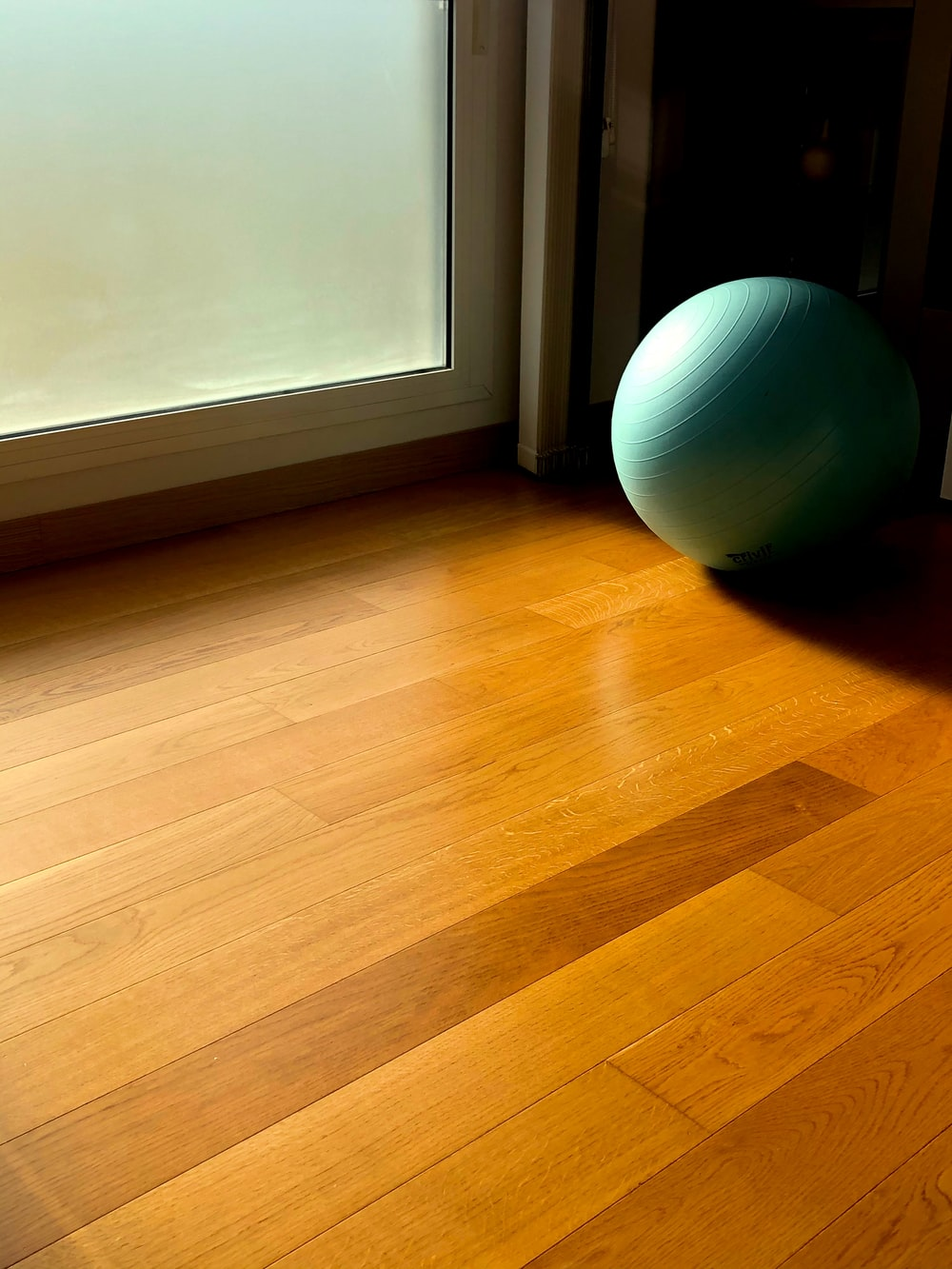 green fitness ball on parquet floor