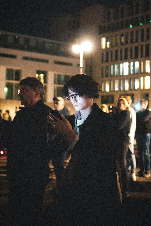 man wearing black blazer using smartphone