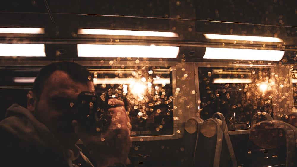 man using camera inside train