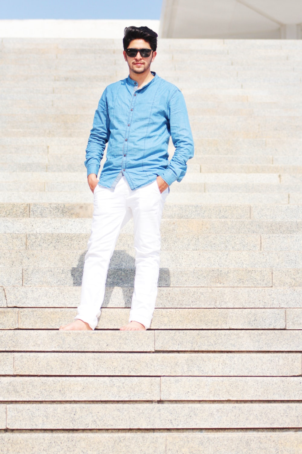 man wearing blue dress shirt and white jeans