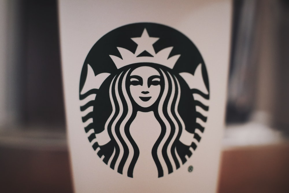selective focus photography of black and white Starbucks cup