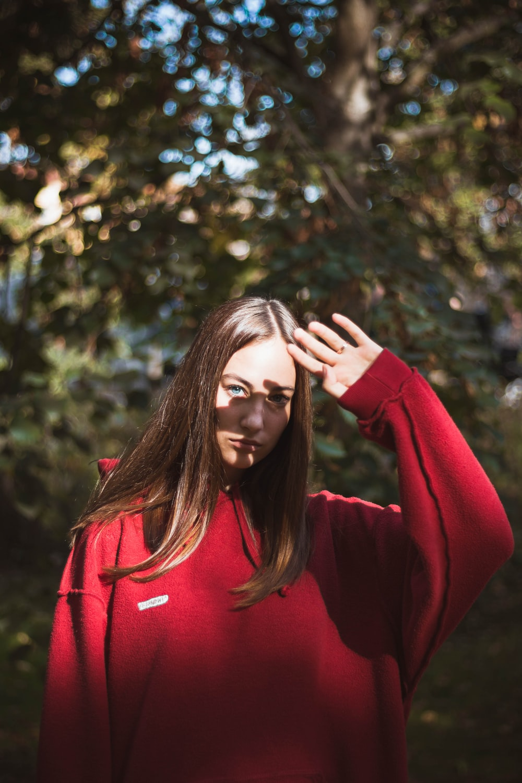 woman wearing red sweater standing beside tree