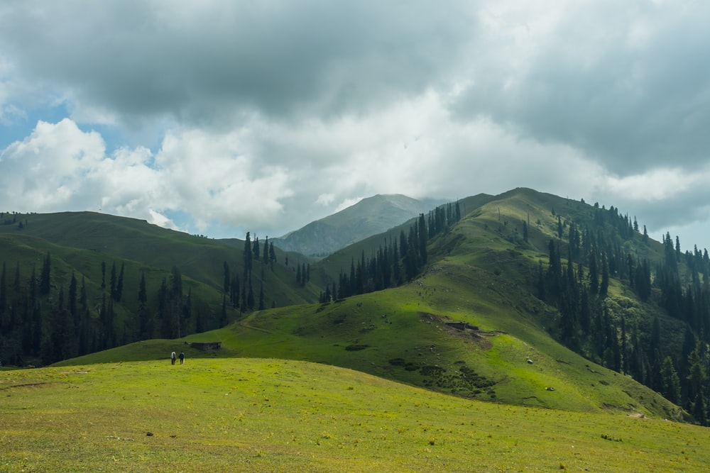 green mountain during daytime under white clouds
