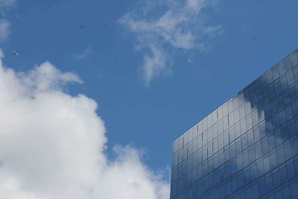 glass building under white and blue sky