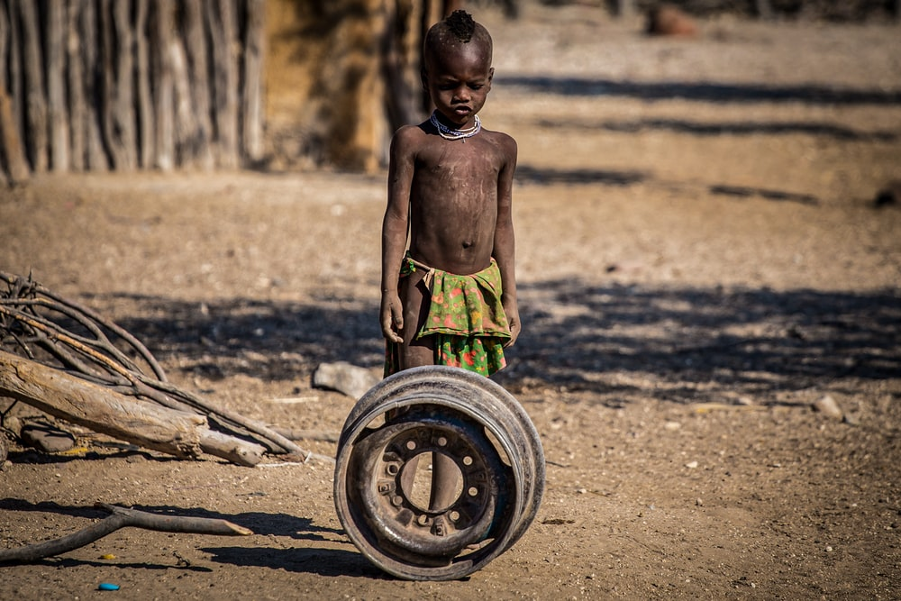 child standing beside chrome wheel