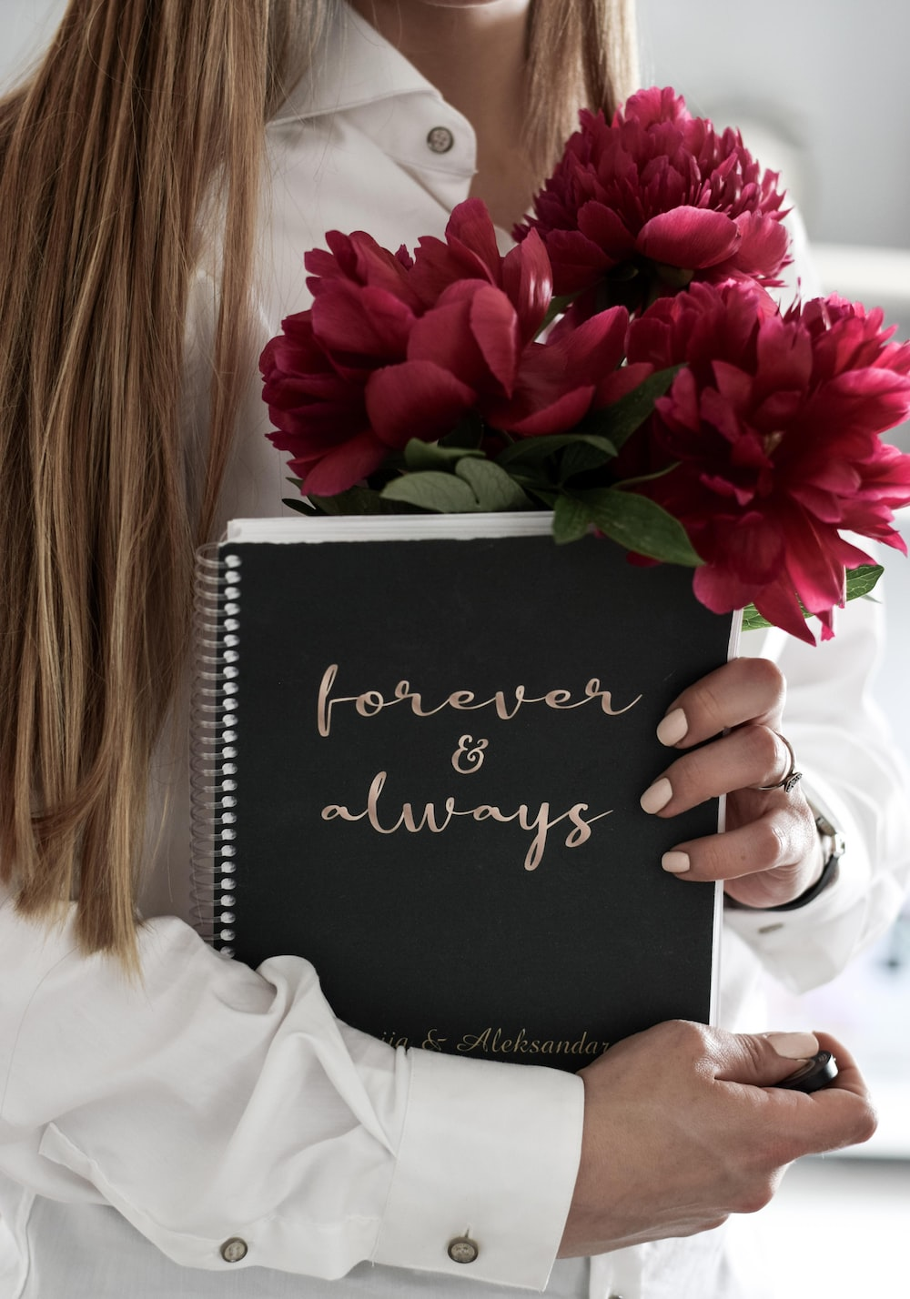 woman wearing white blouse carrying flower and book