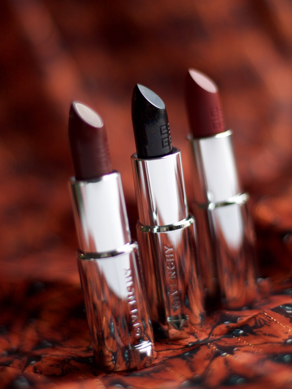 selective focus photography of three assorted-color lipsticks