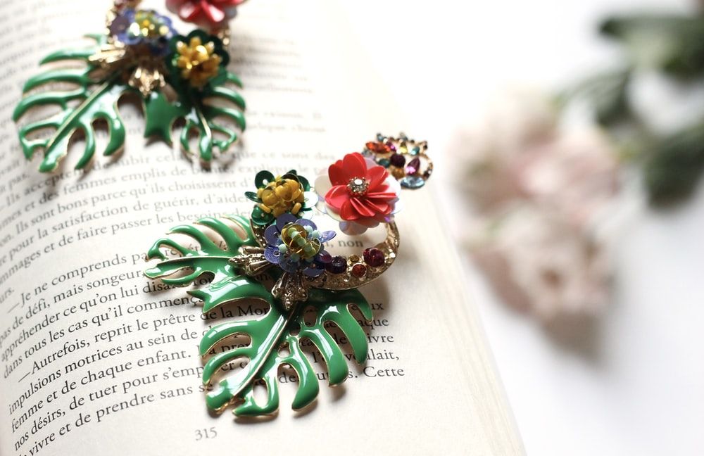 two multicolored floral brooch