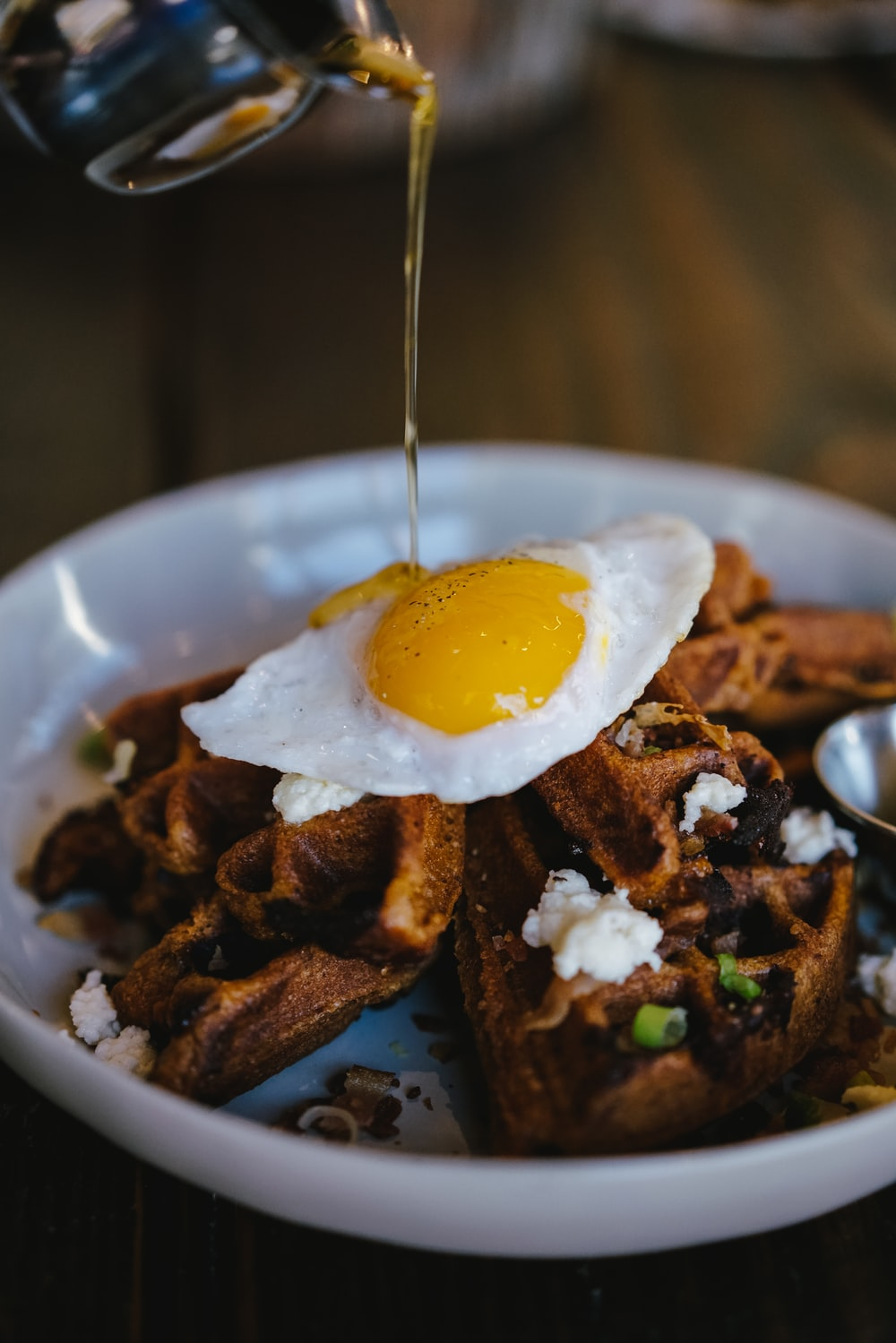 person pouring maple syrup on bowl of waffle with sunny side up egg