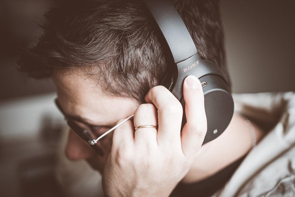 man using black Sony headphones