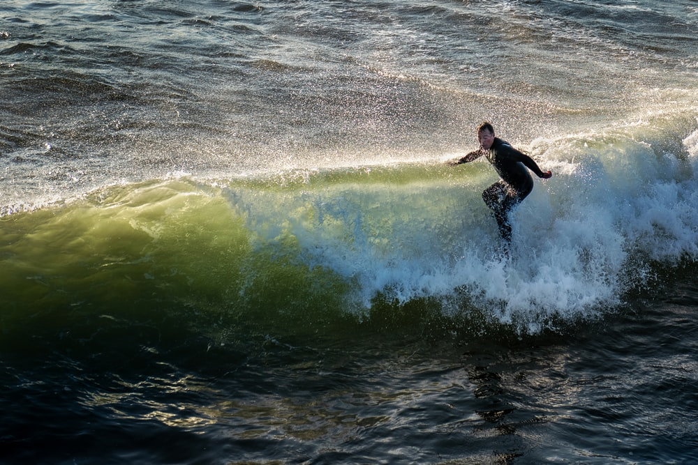 time lapse photography of man surfing in the beach