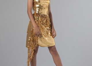 woman wearing gold sequined sleeveless dress with fringe