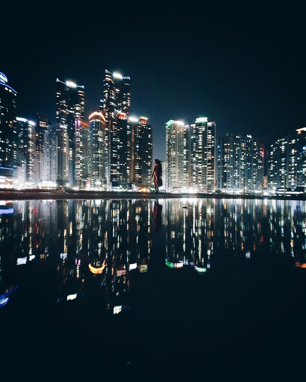 reflection of high-rise buildings on body of water during nighttime
