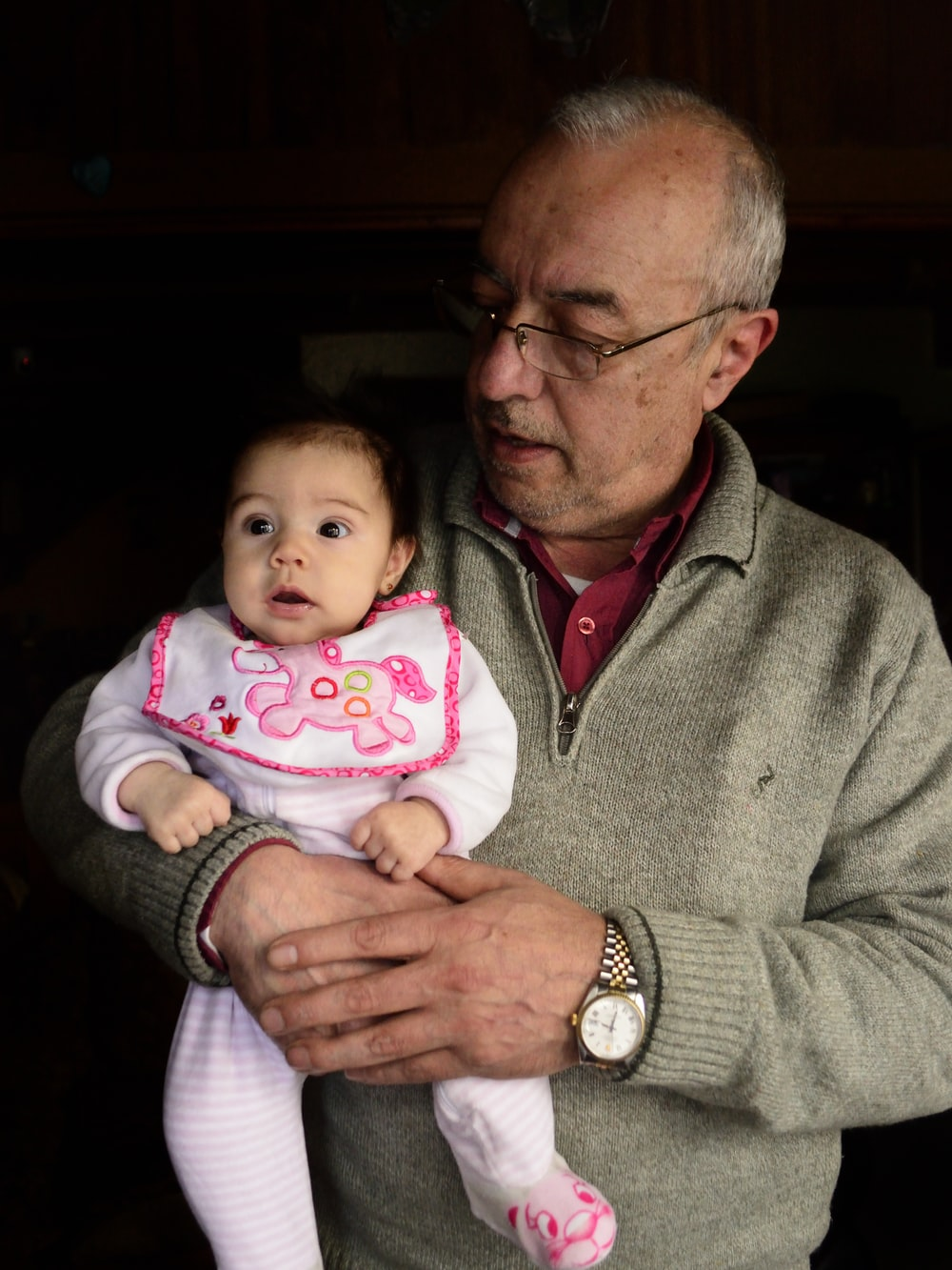 man carrying a baby girl in his arms
