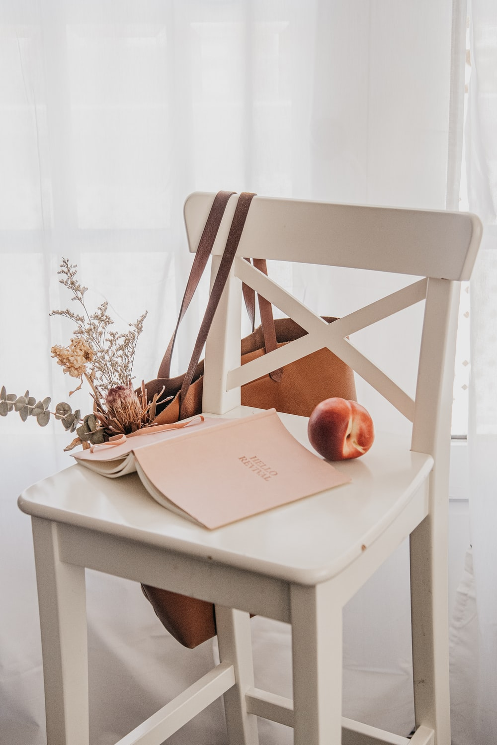 book and apple on white wooden chair
