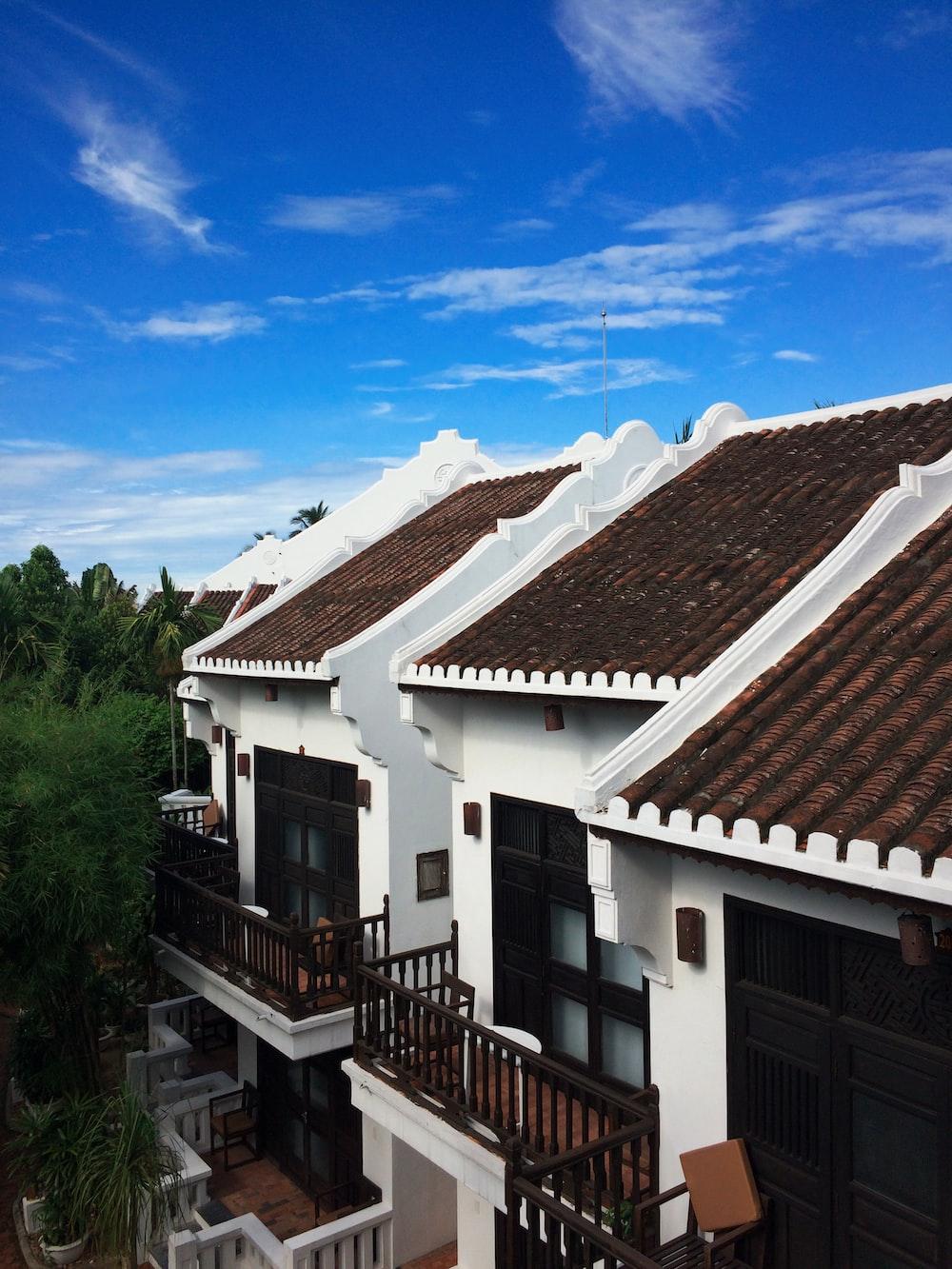 white and brown concrete house under a calm blue sky